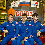 In the Integration Facility at the Baikonur Cosmodrome in Kazakhstan, Expedition 44 crew members Kjell Lindgren of NASA (left), Oleg Kononenko of the Russian Federal Space Agency (Roscosmos, center) and Kimiya Yui of the Japan Aerospace Exploration Agency (right) pose for pictures in front of their Soyuz TMA-17M spacecraft July 11 during a fit check dress rehearsal session. The trio will launch July 23, Kazakh time from Baikonur for a five-month mission on the International Space Station. Credit: Gagarin Cosmonaut Training Center.