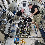 ISS043E181459 (05/07/2015) – NASA astronauts Scott Kelly (left) and Terry Virts (right) work on a Carbon Dioxide Removal Assembly (CDRA) inside the station