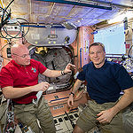 ISS043E198419 (05/15/2015) --- NASA astronauts Scott Kelly (left) and Terry Virts (right) share a snack while inside the station