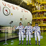 In the Integration Facility at the Baikonur Cosmodrome in Kazakhstan, Expedition 44 crew members Kjell Lindgren of NASA (left), Oleg Kononenko of the Russian Federal Space Agency (Roscosmos, center) and Kimiya Yui of the Japan Aerospace Exploration Agency (right) wave to reporters by the upper stage of their Soyuz booster rocket July 11 prior to a fit check dress rehearsal session. The trio will launch July 23, Kazakh time from Baikonur in their Soyuz TMA-17M spacecraft for a five-month mission on the International Space Station. Credit: Gagarin Cosmonaut Training Center