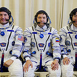 In the Integration Facility at the Baikonur Cosmodrome in Kazakhstan, Expedition 44 crewmembers Kjell Lindgren of NASA (left), Oleg Kononenko of the Russian Federal Space Agency (Roscosmos, center) and Kimiya Yui of the Japan Aerospace Exploration Agency (right) pose for pictures July 11 prior to a fit check dress rehearsal session. The trio will launch July 23, Kazakh time from Baikonur in their Soyuz TMA-17M spacecraft for a five-month mission on the International Space Station. Credit: Gagarin Cosmonaut Training Center.